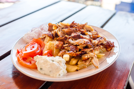 Greek gyros with french fries, vegetables and tzatziki sauce on white plate
