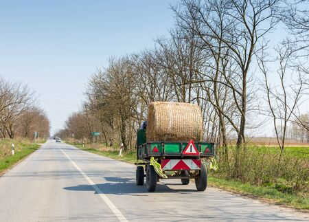 Small truck carries one hay roll along asphalt road