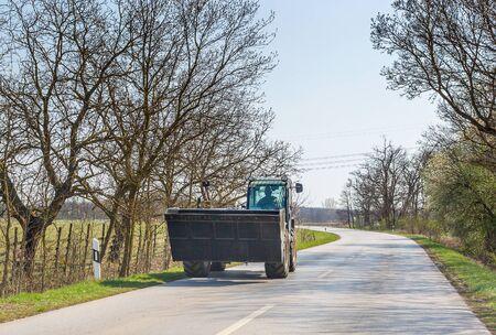 Excavator moves on asphalt road in spring