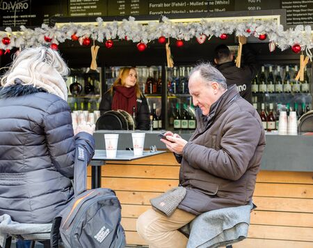 Budapest, Hungary - December 31, 2018: Elderly man uses a mobile phone sitting at table in street cafe with cup of mulled wine. Annual Christmas fair on Szent Istvan square in Budapest, Hungary