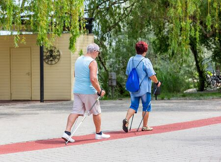 Senior couple walking with hiking sticks on treadmill along lake in city park