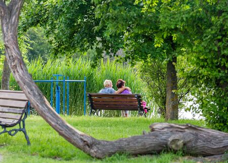 Nyiregyhaza, Hungary – April 19, 2019: Happy senior couple sitting on bench in park. Man and woman resting by the lake Publikacyjne