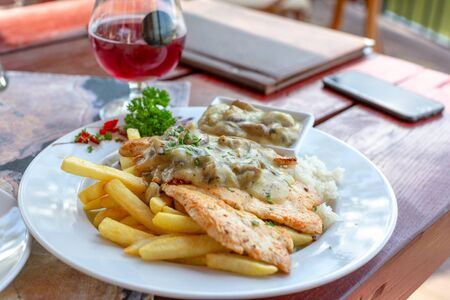 Grilled chicken fillet in white mushroom sauce with french fries on white plate. Glass of red wine in the background Imagens