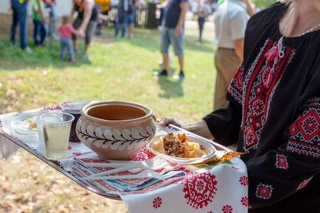 Woman in black national blouse embroidered with red and white threads holding a tray covered with embroidered towel. Traditional Ukrainian food borscht and dumplings on a tray