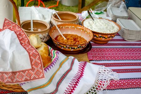 Traditional ukrainian garlic bread (pampushky) and dumpling sauces (sour cream, melted butter, fried onions with cracklings) in rustic clay ceramic pot on a table covered with embroidered tablecloth