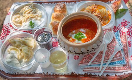 Traditional Ukrainian food borscht and dumplings on a tray covered with embroidered towel