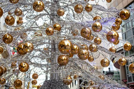 Unusual Artificial Christmas tree made of metal branches braided by light bulbs garland with yellow balls in center of city