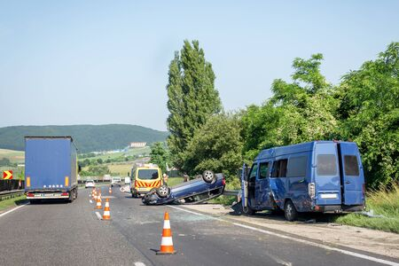 Car crash accident on highway. Damaged blue minibus after collision, overturned car and ambulance car on roadside. Traffic cones at accident site