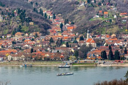 Beautiful view of small town Nagymaros in highlands on other side of Danube river, Hungary. Small ferry crosses the river Stock fotó