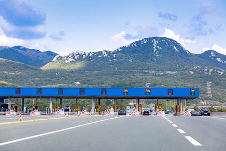 Cars passing on toll road. Point of payment on highway. Beautiful mountain landscape on background. Bitoraj mountains, Gorski Kotar, Croatia. Space for text