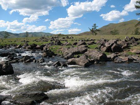 Rapid River runs among the rocks against the blue sunny sky Stock Photo - 13069160