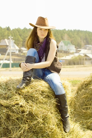 A young girl sits in the style of a cowboy in the hay photo