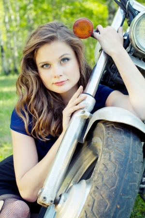 Young beautiful girl sits near the front wheel motorcycle photo