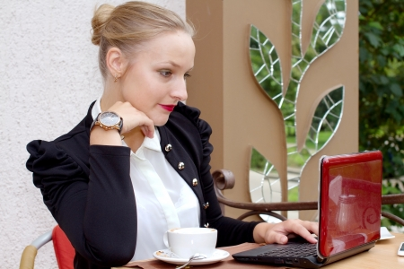 Young sexy businesswoman working on a notebook in a outdoor cafe with a cup of coffee photo