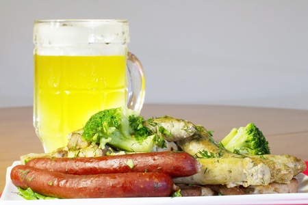 Plate with several kinds of sausages, slices of grilled meat and cauliflower, and some glass of light beer photo