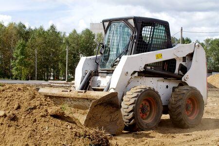 gaining: Small bulldozer is gaining ground in the bucket