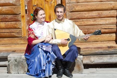 Ni�a hermosa y el chico con la balalaika en el traje nacional ruso sentado en el porche de una casa de madera