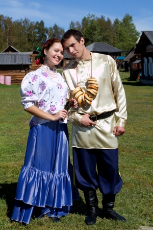 A young man with a bunch of bagels and beautiful girl with a wooden spoon in the national costumes of Cossack Stock Photo - 15511284
