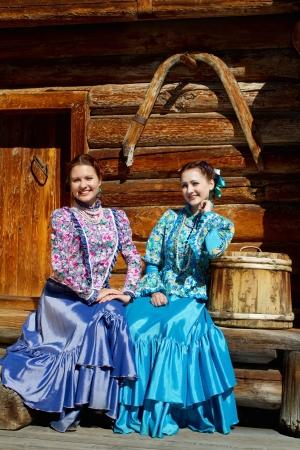 Two young pretty girls sitting on a wooden bench photo