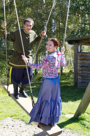 national costume: A girl and a young boy in national costume Cossack swinging on a swing