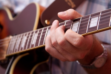Man s hand, playing the guitar