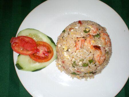 Arroz con verduras, gambas y rodajas de pepino y tomate en un plato