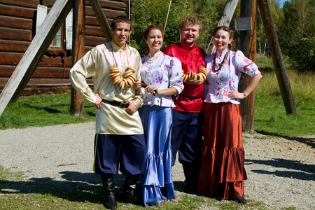 Two young men with bundles of bagels and two beautiful girls in traditional Russian costumes photo