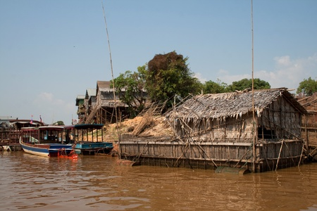 Floating house in a village in Cambodia and two boats Stock Photo - 16365748