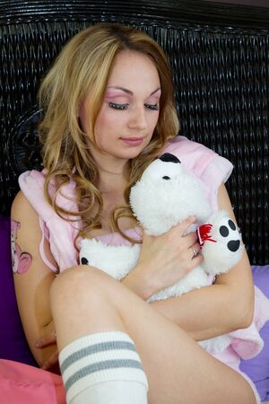 Girl holding plush toy and looking at it