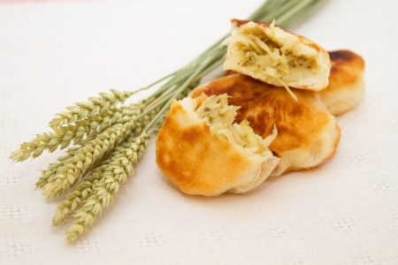 Fried cakes with cabbage and wheat ears on a white napkin