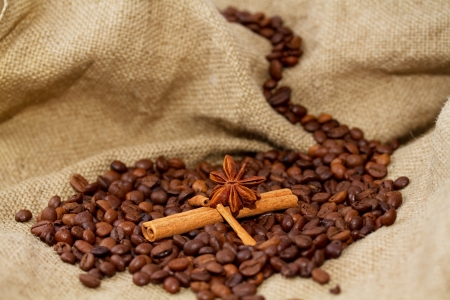 Mountain lake of coffee beans and cinnamon sticks in a boat Stock Photo