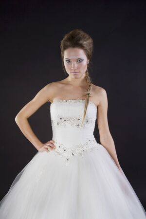 Young beautiful girl in a wedding dress on a dark background Stock Photo - 17280793