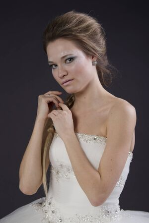 Young beautiful girl in a wedding dress on a dark background photo