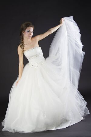 Young beautiful girl in a wedding dress on a dark background Stock Photo - 17280789
