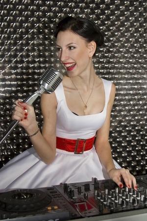La chica joven encantadora canta para las cubiertas de DJ