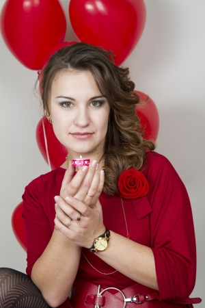suppository: Young attractive girl holding a lighted candle on a background of red balloons