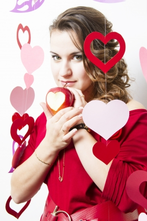 Attractive young girl standing among ornaments from paper hearts and holds a ripe apple with carved heart symbol photo