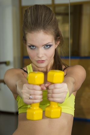 The girl is engaged in fitness and exercise with dumbbells