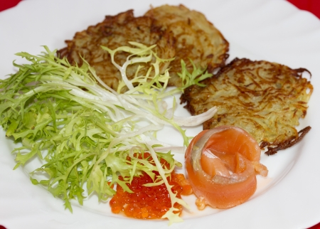 Potato pancakes on a plate with a piece of salmon and red caviar photo