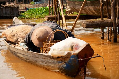The man reached down to the bottom of the boat, filled many bags and baskets Stock Photo - 18494435