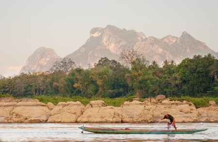 A fisherman in a long boat on the Mekong River amid the big mountain Stock Photo - 18494492