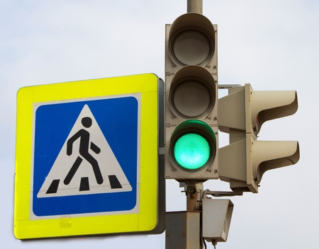 Crosswalk sign and traffic light showing green light for cars photo