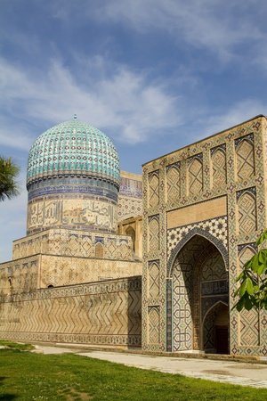 A large gate and a tower with a dome of an ancient madrasah in Samarkand, Uzbekistan