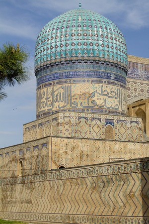 A tower with a dome of an ancient madrasah in Samarkand, Uzbekistan photo
