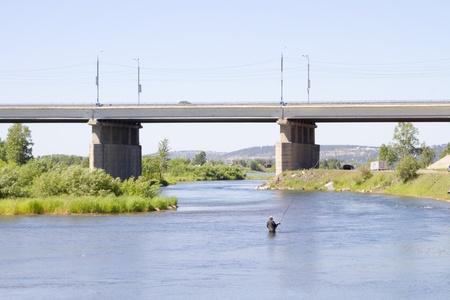 A fisherman with a fishing rod on the Angara River, near Irkutsk