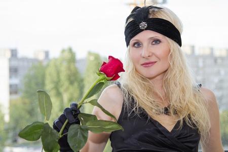 La chica en un vestido negro con un adorno en la cabeza y rosas rojas