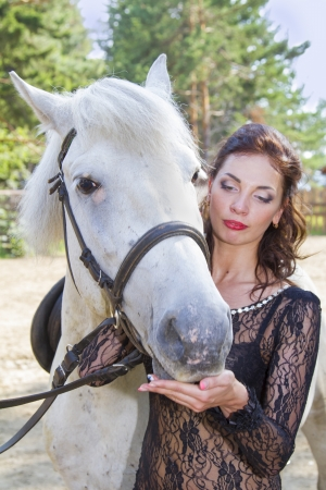 Slender pretty girl in a black dress takes care of the horse photo