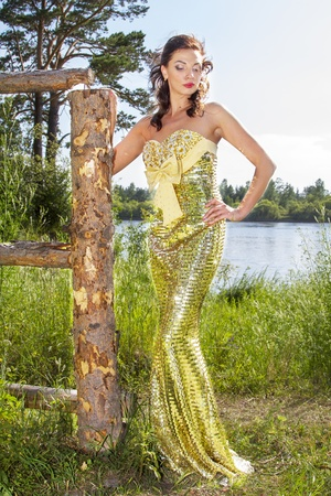 Sexy charming girl in a gold color dress