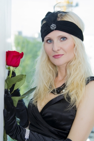 The girl in a black dress with an ornament on her head and red roses photo