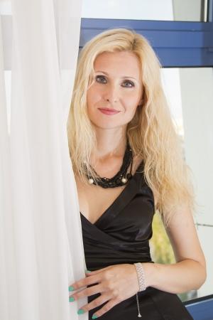 Young beautiful girl in black dress near the window